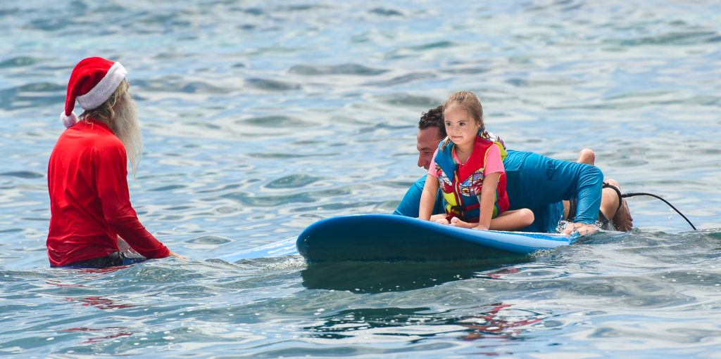 little girl with down syndrome riding on a paddle board  at s4sn event in kona, hawaii